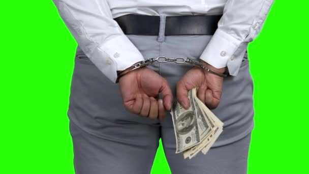 Arrested man in handcuffs holding money.