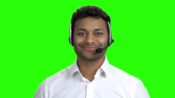 Smiling call center operator on green screen.