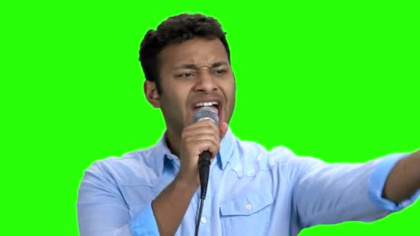 Enthusiastic man singing with microphone on green screen.