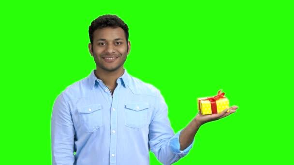 Pohledný indický muž prezentuje dárkovou schránku.