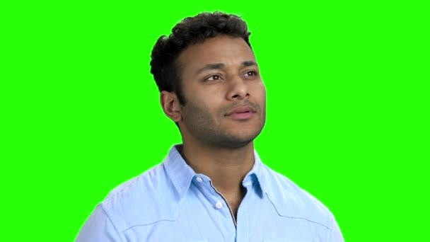 Happy thoughtful Indian guy on green screen.