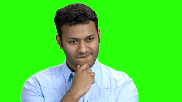 Young man with thoughtful expression on green screen.