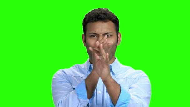 Young man making funny face on green screen.