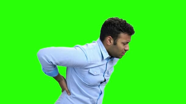 Young man with pain in kidneys on green screen.