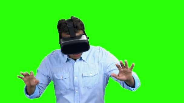 Young scared man wearing virtual reality glasses.