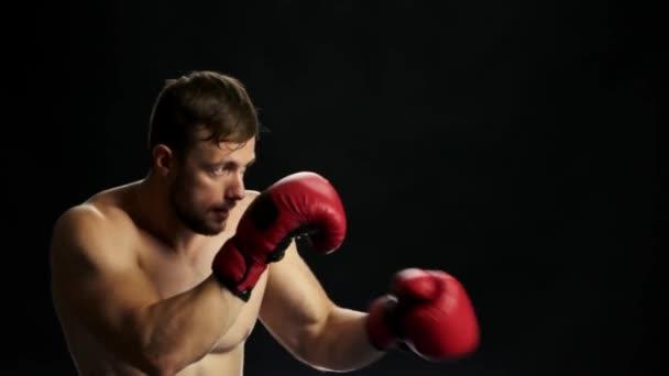 Mladý boxer trénuje na černém pozadí.