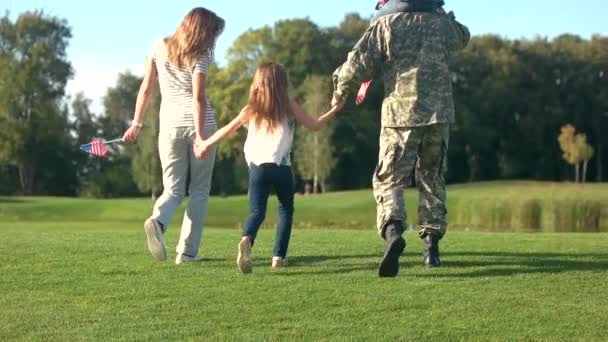 Back view walking family with father in military camoubackgrounde.