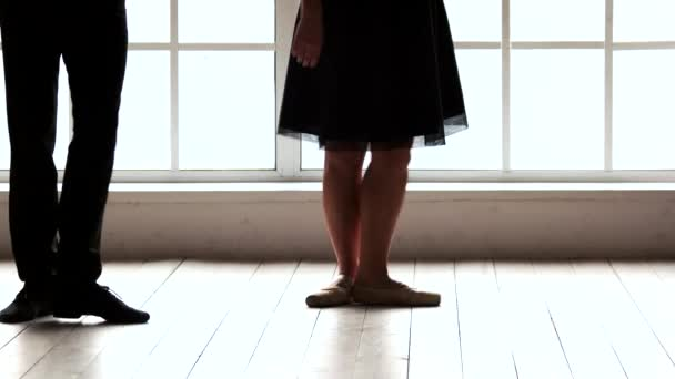 Legs of dancers working out in ballet studio.