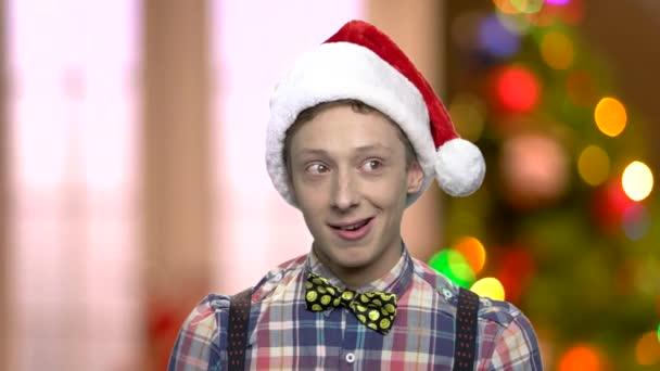 Lustige Teenager mit Weihnachtsmütze.