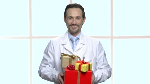 Smiling doctor presenting gift boxes.