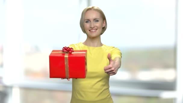 Cheerful woman giving gift box and thumb up.