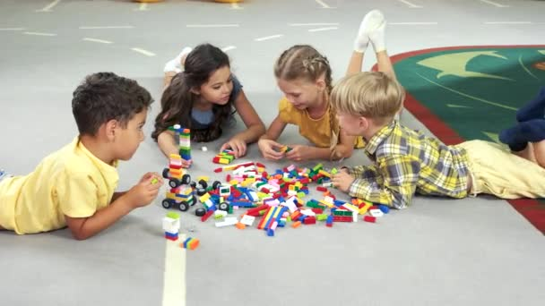 Four kids play with blocks.
