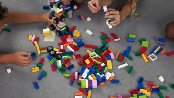 Kids playing with colorful constructor on the floor.