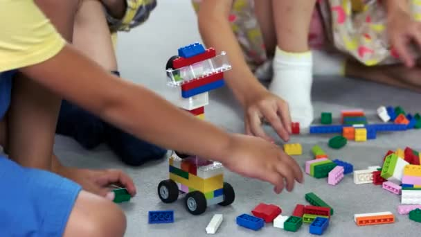 Close up kids playing with block toys in nursery school.