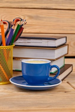 Books, pencils and coffee cup.