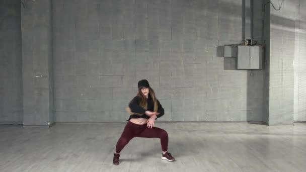 Female modern style dancer dancing in studio.