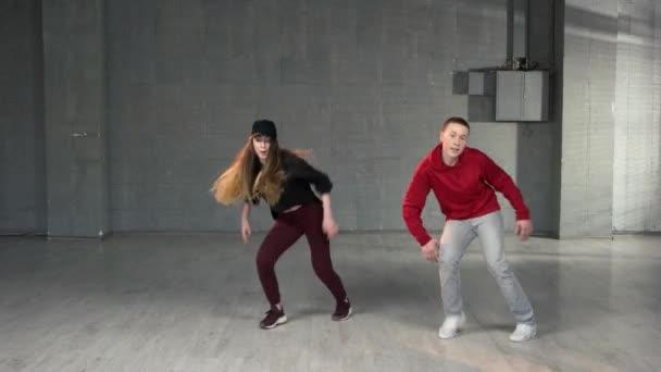 dva mladí muži a ženy tančí hip-hop.