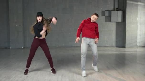 Dvojice teenagerů tančících v interiérech.