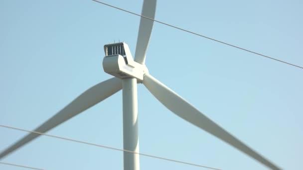 Nahaufnahme einer Windkraftanlage, die sich auf blauem Himmel dreht.