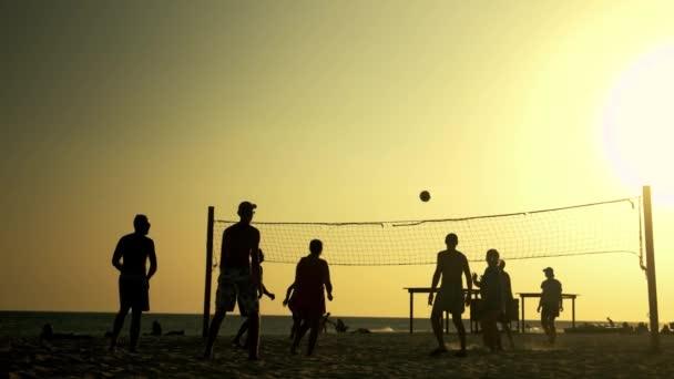 Lidé hrají volejbal na pláži při západu slunce.