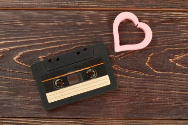 Old analogue cassette and pink heart. Tape cassette and heart-shaped decoration on brown wooden background. Old musical technology and love concept. stock vector