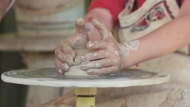 Hände von Mädchen arbeiten auf Töpferrad.