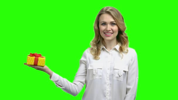 Žena, která drží dárkové pole na zelené obrazovce.