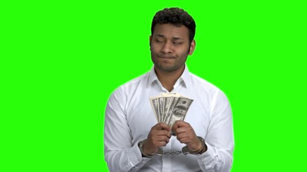 Businessman in handcuffesd holding dollar bribe.