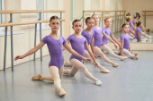 Young ballerinas stretching on the floor.