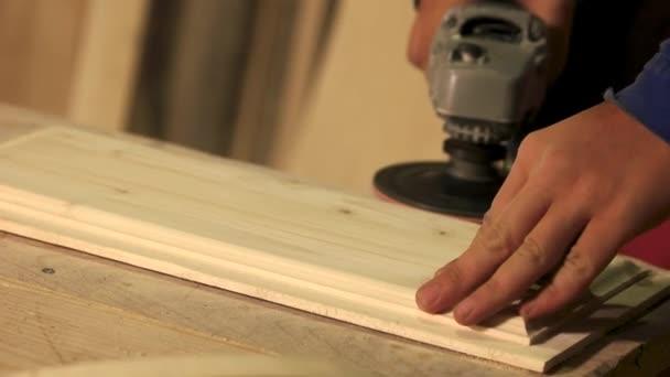 Tesař vyhlazuje povrch dřevěné desky.