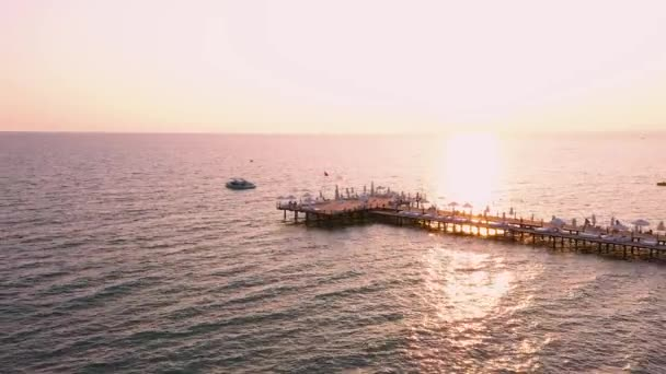 Aerial view of wooden pier in sea during sunset.