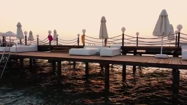 Wooden pier with sunbeds and umbrellas in the sea.