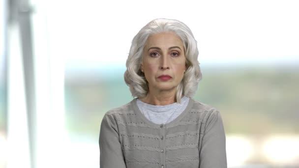 Starší žena se zamyšleným výrazem.