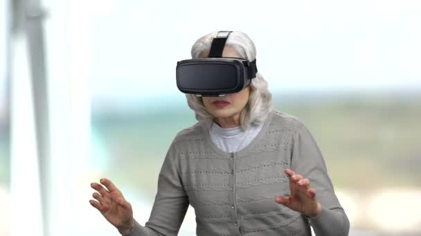 Old woman wearing virtual reality headset.