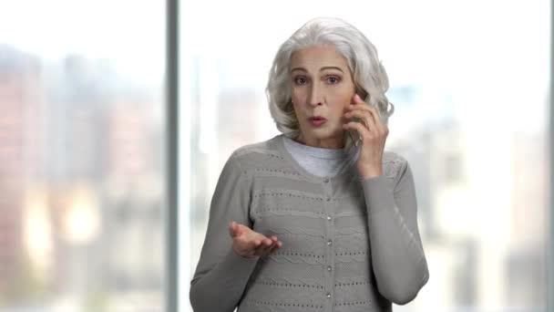 Starší žena mluvila na průhledném telefonu.