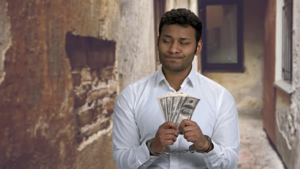 Arrested businessman holding hundred dollar bills.