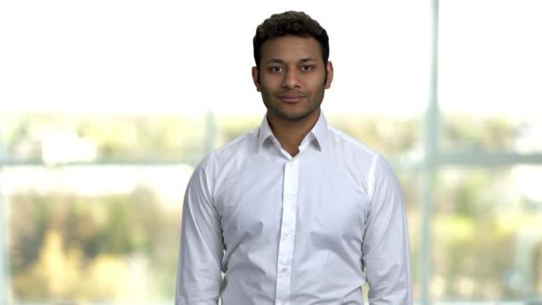 Usmívající se indický podnikatel se dívá do kamery.