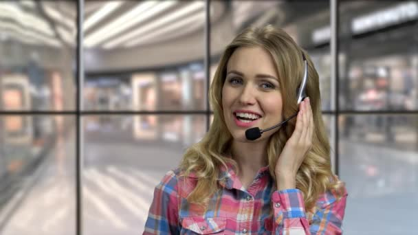 Close up smiling call center operator talking with a client.