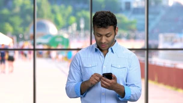Mladý pohledný muž pomocí aplikace na svém smartphonu.
