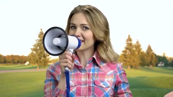 Zblízka mladá potěšená žena mluví do megafonu.
