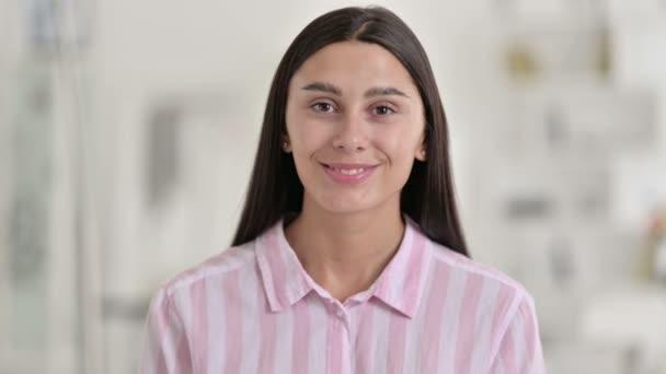 Porträt einer fröhlichen jungen Lateinerin, die in die Kamera winkt