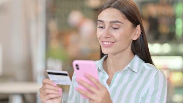 Fiatal latin nő portréja sikeres online fizetéssel okostelefonon