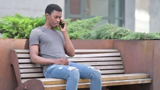 Junger Afrikaner spricht auf Bank mit Smartphone