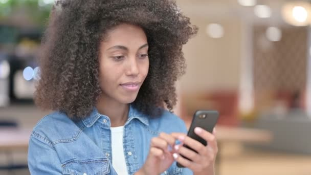 African Woman Celebrating Success on Smartphone