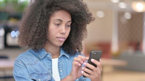 Africká žena pomocí smartphonu, prohlížení internetu