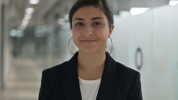 Porträt einer jungen indischen Geschäftsfrau, die Herzzeichen mit der Hand zeigt