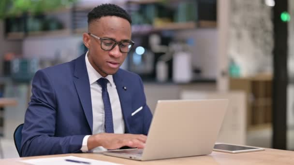 Aufgeregter afrikanischer Geschäftsmann feiert Erfolg auf Laptop im Büro