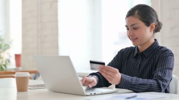 Junge Inderin mit Erfolg beim Online-Bezahlen am Laptop
