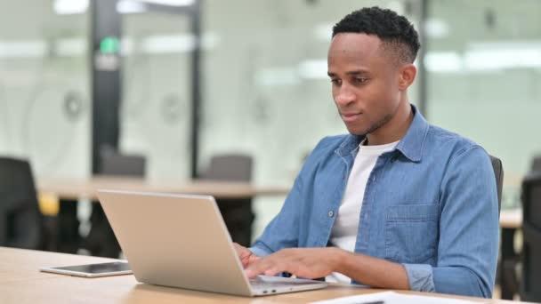 Fröhlicher Afrikaner mit Laptop lächelt in die Kamera