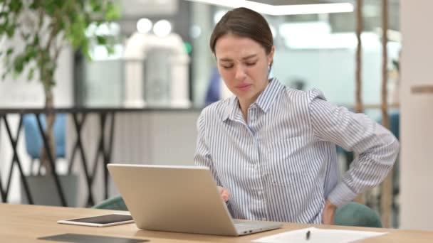 Müde junge Frau mit Laptop hat Rückenschmerzen im Büro